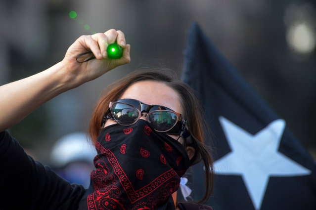 A demonstrator points a green laser light to riot police during a protest against the government of President Piñera on November 27, 2019 in Santiago, Chile. Earlier today, President Piñera urged Congress to approve bills to reduce social unrest by banning hooded protesters, looting and barricades. He insisted on bringing military to the streets to protect public goods without calling state of emergency. Protests continue uninterruptedly since October 18 when a raise in metro fare was announced. Demonstrators demand urgent measures to reduce inequality, a raise in pensions and minimum salary, fair prices in public services and improvements in education and health care.(Photo by Claudio Santana/Getty Images)