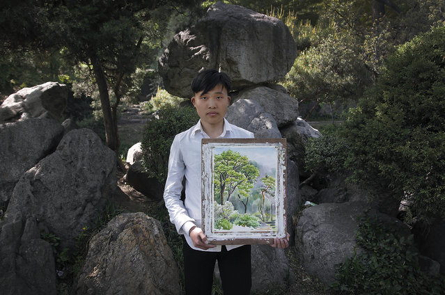 Pak Sin Hyok, 16, a student of the Pyongyang University of Fine Art poses with his unfinished water-color painting of trees in the Moranbong or Moran Hill, Sunday, May 10, 2015, in Pyongyang, North Korea. Pak has been studying art for 3-years and hopes to be a professional artist after he graduates in this course that lasts for 9-years. (Photo by Wong Maye-E/AP Photo)