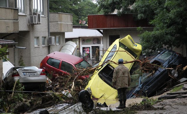 A man looks over piled up cars swept away by severe flooding in the town of Varna, Bulgaria, Friday, June 20, 2014. Bulgarian authorities say ten people have died and several others are missing after heavy rain and flooding hit the Black Sea port city of Varna. Large parts of the Balkan country have been hit by heavy rain and hailstorms, and hundreds of people have been left without electricity and food supplies. (Photo by AP Photo/ImpactPressGroup)