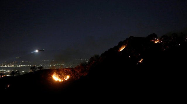 """A helicopter flies over a hotspot while battling the """"Old Fire"""" burning in Calabasas, California U.S., June 4, 2016. (Photo by Mario Anzuoni/Reuters)"""