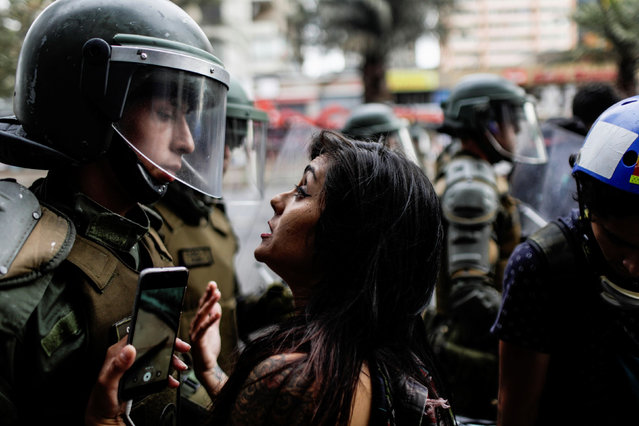 A woman confronts a member of the security forces during a protest against Chile's government in Santiago, Chile on December 19, 2019. (Photo by Ricardo Moraes/Reuters)