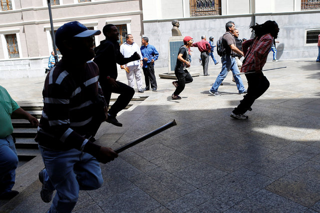 Supporters of Venezuela's President Nicolas Maduro run after an opposition lawmaker during a protest at the area of the elections council headquarters in Caracas, Venezuela, June 9, 2016. (Photo by Ivan Alvarado/Reuters)