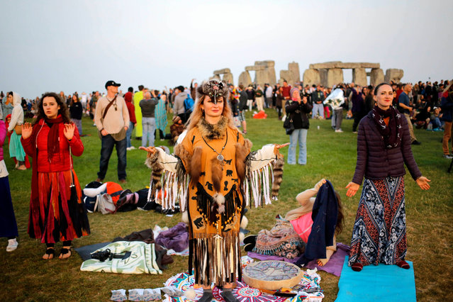 A shaman waits for the sun to rise on the summer solstice during the annual festival at Stonehenge, Salisbury, Britain, 21 June 2017. (Photo by Kim Ludbrook/EPA)