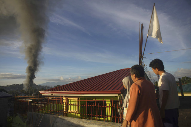 A resident looks at a burning structure during early morning airstrikes by government forces in the continuing fight for Marawi city by Muslim militants Friday, June 23, 2017, in southern Philippines. The siege by militants aligned with the Islamic State group continues as it enters its second month Friday. (Photo by Linus Guardian Escandor II/AP Photo)