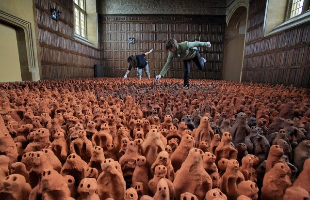 """Volunteers Francis Aitken, right, and Deborah Westmancote put in place some of the thousands of clay figures that make up Antony Gormley's """"Field for the British Isles"""" artwork, in Barrington Court, near Ilminster, England, April 25. The acclaimed work, on loan from the Arts Council Collection, consists of 40,000 clay figures. It is being exhibited in three normally empty rooms of the Barrington Court, a Tudor manor house belonging to the Britain's National Trust, an organization that preserves outdoor spaces and historic buildings in the U.K."""