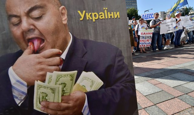 People rally near a placard depicting a banker counting money set in front of Ukrainian parliament in Kiev during protest action of borrowers of Ukrainian banks on July 1, 2014. The borrowers, who took credits in the western currency for the construction or purchase of housing, protest against the policy of the banks which make enormous profits at the expense of borrowers after the depreciation of the Ukrainian currency, they claim. (Photo by Sergei Supinsky/AFP Photo)