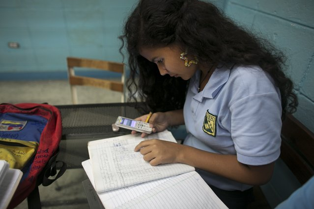In this May 30, 2016 photo, Maria Arias, 14, quickly uses the calculator on a friend's cell phone to figure out why she has errors on her homework, during her accounting class at a public high school in Caracas, Venezuela. Arias' accounting teacher recently went missing for a week and a half, and when she showed up again, she limited herself to correcting homework. (Photo by Ariana Cubillos/AP Photo)