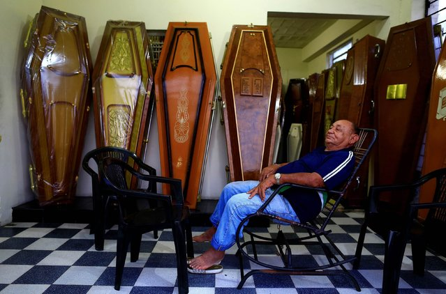 """A man rests in front of his funeral shop in Olinda, near Recife, on June 27, 2014. In a project called """"On The Sidelines"""" Reuters photographers share pictures showing their own quirky and creative view of the 2014 World Cup in Brazil. (Photo by Tony Gentile/Reuters)"""