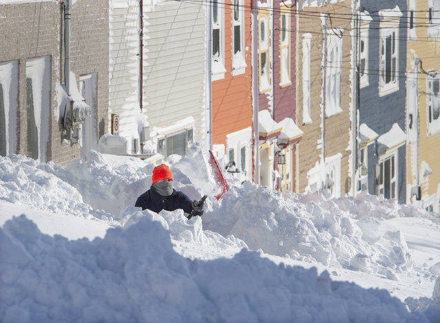 A resident digs out his walkway in St. John's Newfoundland on Saturday, January  18, 2020. The state of emergency ordered by the City of St. John's is still in place, leaving businesses closed and vehicles off the roads in the aftermath of the major winter storm that hit the Newfoundland and Labrador capital. (Photo by Andrew Vaughan/The Canadian Press via AP Photo)