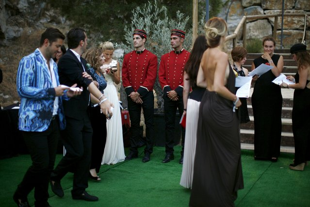 Bellhops stand while people arrive to the Starlite Charity Gala in Marbella, near Malaga, southern Spain, August 9, 2015. (Photo by Jon Nazca/Reuters)
