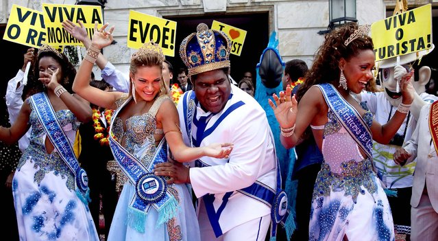 King Momo, the crowned and costumed Milton Rodrigues, flanked by the Carnival queen and two princesses, pose for pictures during carnival celebrations in Rio de Janeiro, Brazil