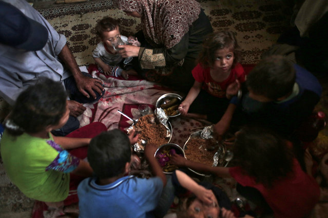In this Monday, June 20, 2016 photo, a Palestinian family breaks their Ramadan fast in their house, in el-Zohor slum on the outskirts of Khan Younis refugee camp, southern Gaza Strip. (Photo by Khalil Hamra/AP Photo)