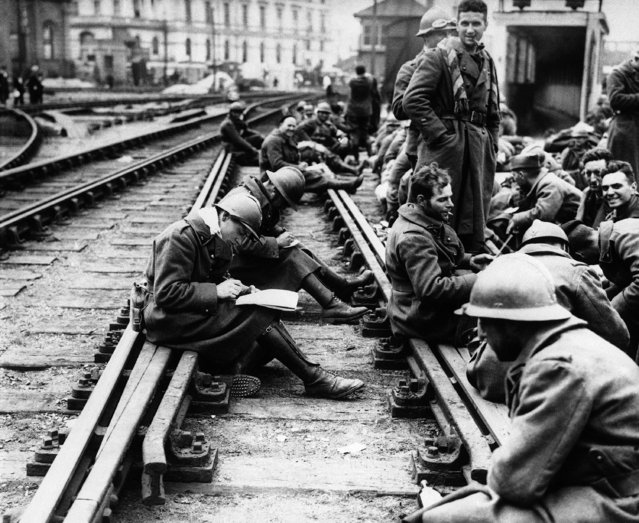 The great withdrawal from Flanders continues and thousands of allied troops are still arriving in England after heroically fighting their way out of Belgium and Northern France. Poilus from the Gallant army of the North sit down by a railway siding to write home the good news of their arrival in England safe and sound on June 3, 1940. (Photo by AP Photo)