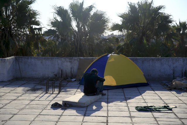 A migrant from Afghanistan sits at the terrace of a deserted hotel on the Greek island of Kos, August 13, 2015. (Photo by Alkis Konstantinidis/Reuters)