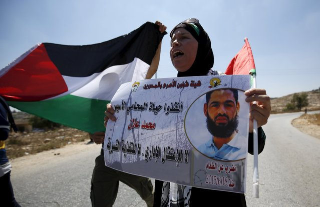 A Palestinian woman holds a picture depicting Palestinian detainee Mohammed Allan during a protest in solidarity with Allan, in the West Bank village of Nabi Saleh, near Ramallah August 14, 2015. A Palestinian detainee in the ninth week of his hunger strike fell unconscious at an Israeli hospital on Friday in a case that could test Israel's new force-feeding law. (Photo by Mohamad Torokman/Reuters)