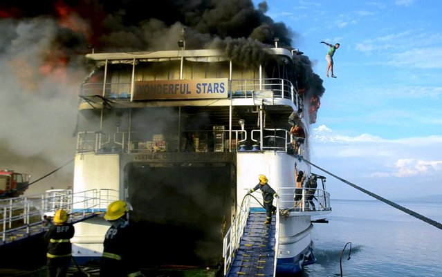 A crew member of the MV Wonderful Stars ship jumps off from the burning ship after a fire broke out at the port in Ormoc city, central Philippines August 15,  2015. (Photo by Ronald Frank Odan Dejon/Reuters)