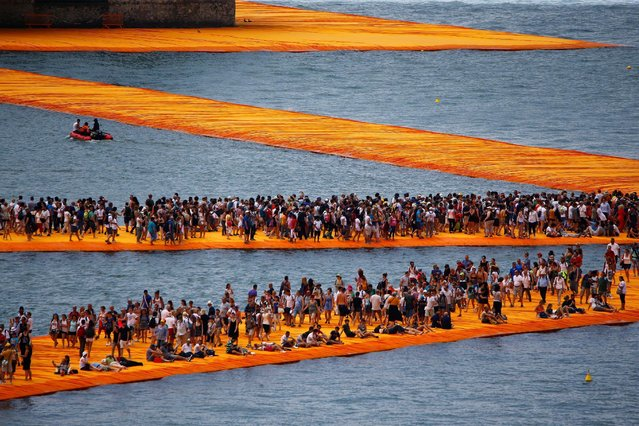 """People walk on the installation """"The Floating Piers"""" on Lake Iseo by Bulgarian-born artist Christo Vladimirov Yavachev, known as Christo, at the installation's last weekend near Sulzano, northern Italy, July 2, 2016. (Photo by Wolfgang Rattay/Reuters)"""