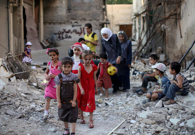 Syrian children walk amidst destruction during an activity organised by a charity group in Jobar, a rebel-held district on the eastern outskirts of the capital Damascus, ahead of Eid al-Fitr holyday in the war-torn country on July 5, 2016. More than 280,000 people have been killed since Syria's conflict began in March 2011 with protests demanding Assad's ouster. Muslims worldwide celebrate Eid al-Fitr marking the end of the fasting month of Ramadan. (Photo by Amer Almohibany/AFP Photo)