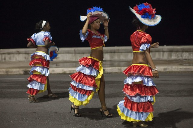 Revellers chat on a street before performing at a carnival parade in Havana August 8, 2014. (Photo by Alexandre Meneghini/Reuters)