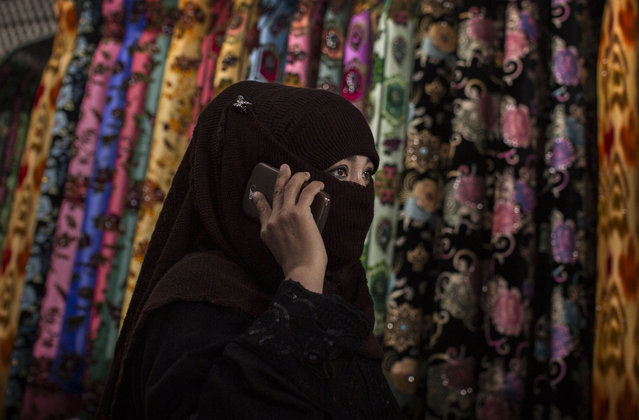 A Uyghur woman wears a veil as she shops at a local market on August 2, 2014 in Kashgar, Xinjiang Province, China. (Photo by Kevin Frayer/Getty Images)