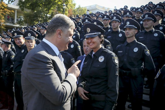 Ukrainian President Petro Poroshenko talks with a police officer during an oath-taking ceremony to launch the work of a new police patrol service, part of the Interior Ministry reform initiated by Ukrainian authorities, in Odessa, August 25, 2015, in this handout photo provided by the Ukrainian Presidential Press Service. (Photo by Markiv Mykhailo/Reuters/Ukrainian Presidential Press Service)