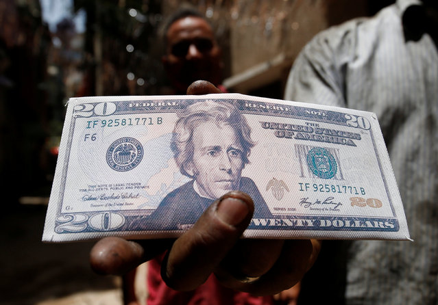 An Egyptian man carries a wallet with the picture of a dollar bill during the holy month of Ramadan in old Cairo, Egypt June 1, 2016. (Photo by Amr Abdallah Dalsh/Reuters)