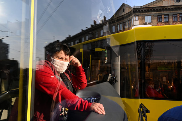 A conductor wearing a face mask looks out from a bus as dozens of people queue at a bus stop after Ukraine limited the number of passengers riding on a bus to 10 as a measure against the spread of the COVID-19 coronavirus, in Kiev on March 19, 2020. (Photo by Genya Savilov/AFP Photo)