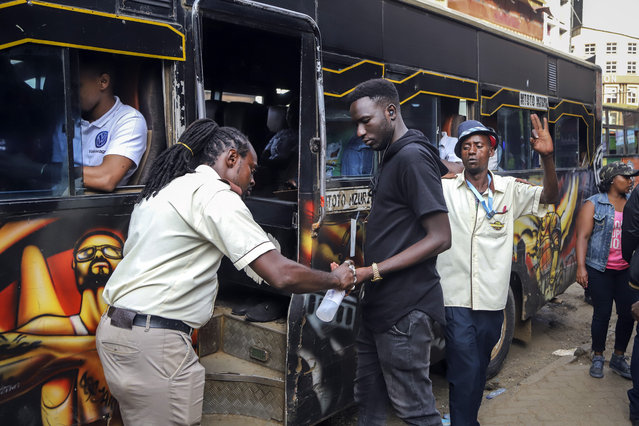 """A bus conductor disinfects the hands of a passenger, after the government directed all operators of """"matatus"""", or public minibuses, to provide hand sanitizer to their clients, on a busy street in downtown Nairobi, Kenya Friday, March 13, 2020. Authorities in Kenya said Friday that a Kenyan woman who recently traveled from the United States via London has tested positive for the new coronavirus, the first case in the East African country. (Photo by Patrick Ngugi/AP Photo)"""