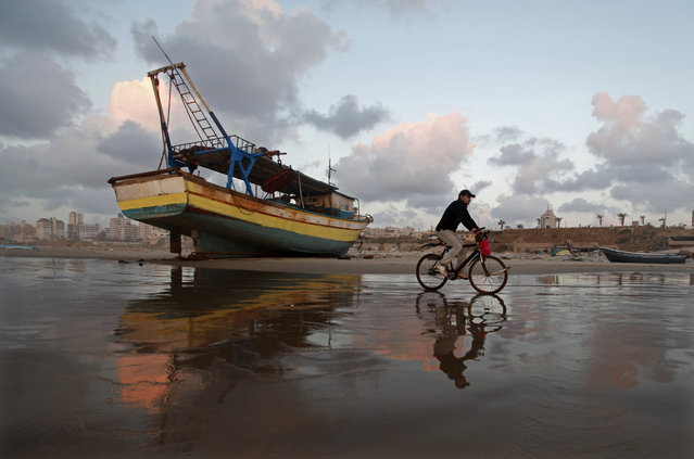 A Palestinian man rides a bicycle on the beach of Gaza City during sunset on Tuesday. April 9, 2013. (Photo by Hatem Moussa/AP Photo)