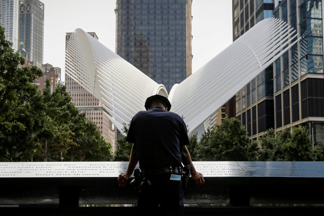 A New York City Police Department (NYPD) officer pauses at the edge of the reflecting pool at the National 9/11 Memorial and Museum during ceremonies marking the 16th anniversary of the attacks in New York, U.S., September 11, 2017. (Photo by Brendan McDermid/Reuters)