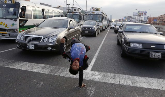 Eleven-year-old Renzo somersaults at a traffic junction in the San Borja district in Lima August 18, 2014. Renzo and his 9-year-old brother Gianpierre perform on streets to make a living from tips given by drivers, make an average of $7 a day  between the two brothers. They work on the streets after school to help their parents, whom they live with, with household expenses. (Photo by Mariana Bazo/Reuters)