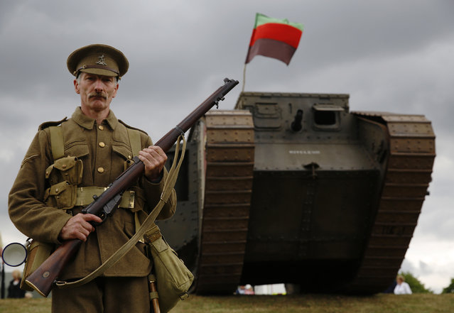 Carpenter Richard Helad, portraying a Lance Corporal of the Queen's Own Royal West Kent Living History Group, participates in a mock WWI battle at the Colchester Military Tournament in Colchester, eastern England July 5, 2014. (Photo by Luke MacGregor/Reuters)