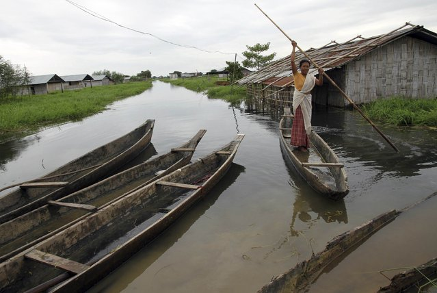 A village woman uses a boat to move to a safer area through the flooded areas of Jorhat district in the northeastern Indian state of Assam August 24, 2014. The latest heavy rains have caused landslides and floods in many parts of India and Nepal. (Photo by Reuters/Stringer)
