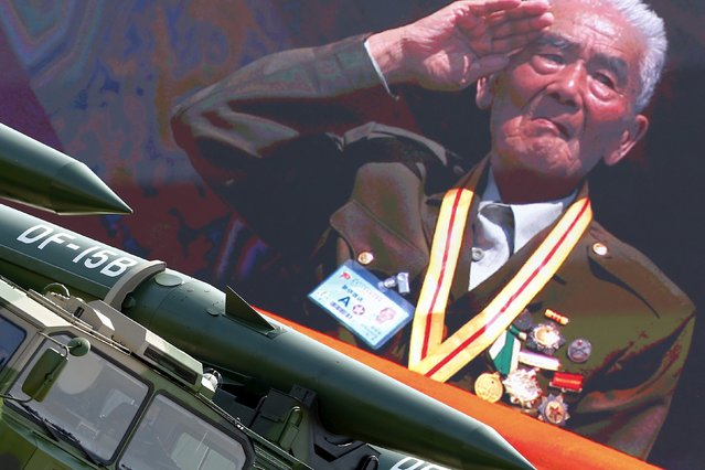 A veteran from a country participating in the military parade marking the 70th anniversary of the end of World War Two is shown on big screen saluting at Tiananmen Square as vehicles with missiles roll past, in Beijing, China, September 3, 2015. (Photo by Damir Sagolj/Reuters)
