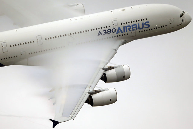 In this June 18 2015 file photo, vapor forms across the wings of an Airbus A380 as it performs a demonstration flight at the Paris Air Show, Le Bourget airport, north of Paris. Airbus sAys it will stop making its costly A380 superjumbo if it can't strike a long-term deal with Emirates airline for a steady supply of the planes. (Photo by Francois Mori/AP Photo)