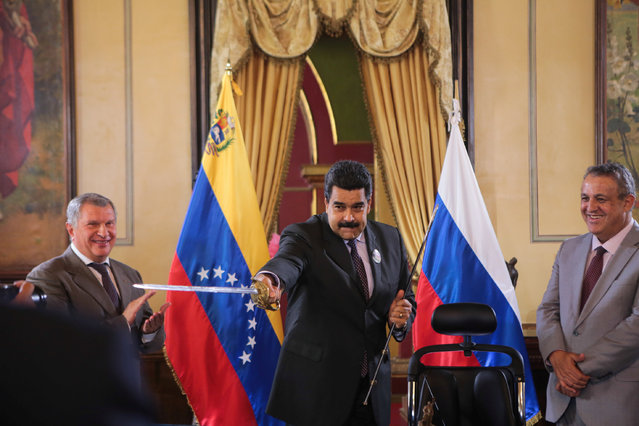 Venezuela's President Nicolas Maduro (C), holds a replica of Venezuela's national hero Simon Bolivar's sword as Head of Russian state oil firm Rosneft Igor Sechin (L) and Venezuela's Oil Minister and President of the Venezuelan state oil company PDVSA Eulogio del Pino look on during an agreement between Rosneft and PDVSA in Caracas, Venezuela July 28, 2016. (Photo by Reuters/Miraflores Palace)