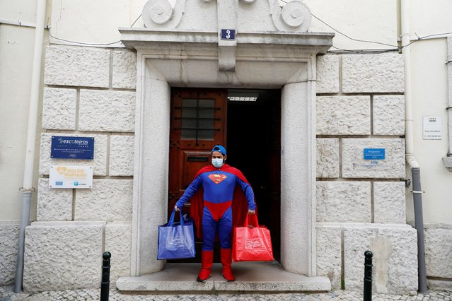 Marcos Rosa, a worker at the Santo Antonio parish council, performs while dressed up as Superman during a special tribute to municipal workers for keeping the city running as the spread of the coronavirus disease (COVID-19) continues, in Lisbon, Portugal on April 25, 2020. (Photo by Rafael Marchante/Reuters)