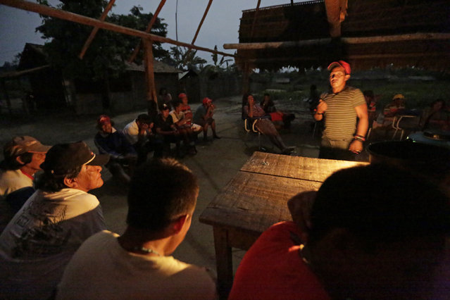 Ka'apor Indian warriors hold a meeting the night before they begin an operation to search for and expel loggers from the Alto Turiacu Indian territory, in the village of Waxiguy Renda near the Centro do Guilherme municipality in the northeast of Maranhao state in the Amazon basin, August 6, 2014. (Photo by Lunae Parracho/Reuters)
