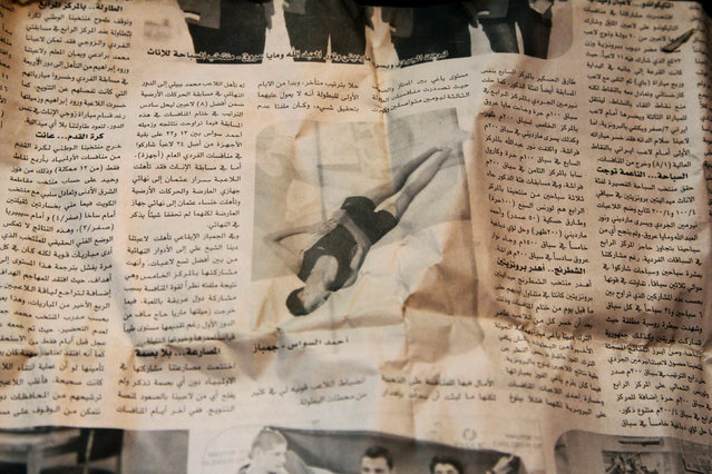Gymnast Ahmad al-Sawas shows a picture in a newspaper, which he says was taken during his participation in the International Sports Games in the Sakha Republic in 2012, as his sits inside his home in the rebel-held Bustan al-Qasr neighbourhood of Aleppo, Syria March 23, 2016. (Photo by Abdalrhman Ismail/Reuters)