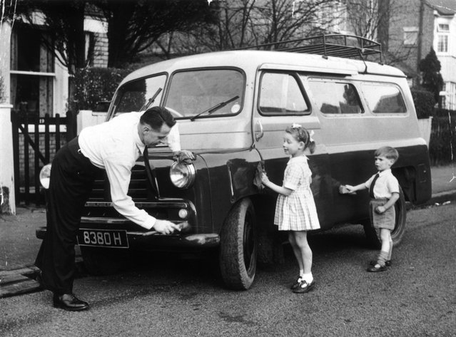 1968, Outside his home, Dennis Uttley polishes the van he bought in order to take groups of deaf children on outings. Helping him are his own two children, Andrew and Jean. (Photo by John Drysdale/Keystone)