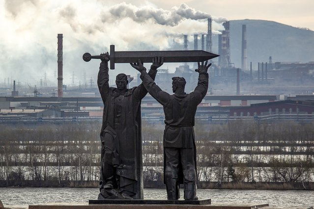 In this photo taken on Wednesday, April 29, 2020, the Rear-Front Memorial sculpted by Lev Golovnitsky and drawn by Yakov Belopolsky, the first part of a triptych also consisting of The Motherland Calls in Volgograd and Warrior Liberator in Treptower Park, Berlin, is seen in Magnitogorsk, Russia. A Magnitogorsk memorial honors both those who fought and those who supplied them. The Rear-Front Memorial shows a soldier and a steelworker holding a sword together, with the worker facing the vast steel mills that were key suppliers to the Soviet defense effort. (Photo by Maxim Shmakov/AP Photo)