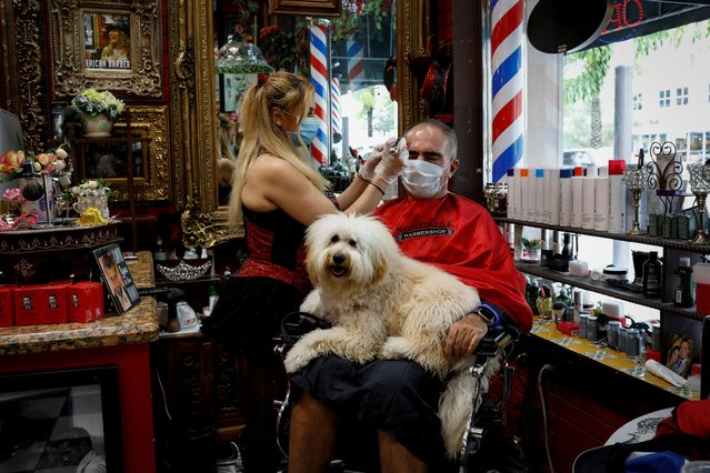 A hairdresser wearing a protective mask cuts the hair of a man at a barber shop, as Miami-Dade County eases some of the lockdown measures put in place during the coronavirus disease (COVID-19) outbreak, in Miami, Florida, U.S., May 18, 2020. (Photo by Marco Bello/Reuters)