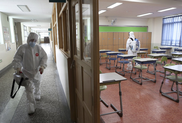 Workers wearing protective gear disinfect as a precaution against the new coronavirus in a class at a high school in Busan, South Korea, Saturday, May 30, 2020. (Photo by Jo Jung-ho/Yonhap via AP Photo)