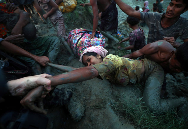 Photographers help a Rohingya refugee to climb out of Naf River as they cross the Myanmar-Bangladesh border in Palong Khali, near Cox's Bazar, Bangladesh on November 1, 2017. (Photo by Hannah McKay/Reuters)
