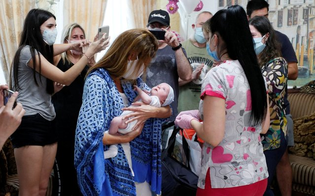 Participants of a ceremony surround Andrea Diez and Fernando Montero, Argentine citizens and parents of newborn Ignacio, during the couple's first meeting with their baby in the Hotel Venice owned by BioTexCom clinic in Kiev, Ukraine on June 10, 2020. The coronavirus disease (COVID-19) lockdown prevented Andrea and Fernando from collecting their baby born to a surrogate mother, after almost all air travel was shut down. (Photo by Gleb Garanich/Reuters)