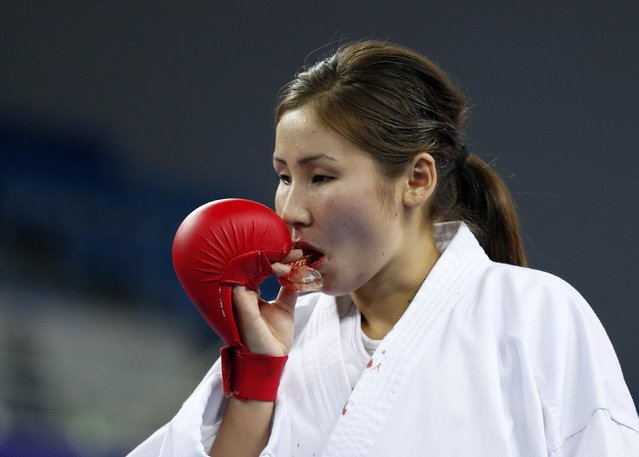 Kyrgyzstan's Elnura Kamchybekova removes a bloody mouth guard in her bronze medal contest against Iran's Nasrin Dousti of the karate competition at Gyeyang Gymnasium during the 17th Asian Games in Incheon October 4, 2014. (Photo by Rob Dawson/Reuters)