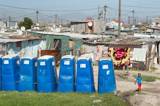 A boy walks past portable toilets at an informal settlement in Khayelitsha, a mostly impoverished township, about 35km from the centre of Cape Town, South Africa on November 10, 2017. (Photo by Rodger Bosch/AFP Photo)