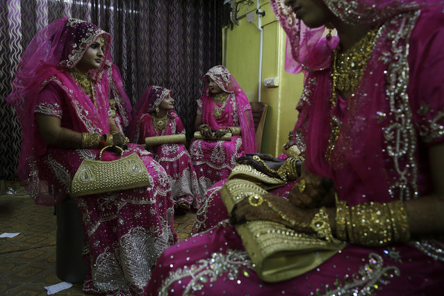 Indian Muslim brides chat as they wait backstage before a mass wedding event in Mumbai, India, Monday, November 20, 2017. Mass weddings in India are organized by social organizations primarily to help the economically backward families who cannot afford the high ceremony costs as well as the customary dowry and expensive gifts that are still prevalent in many communities. (Photo by Rafiq Maqbool/AP Photo)