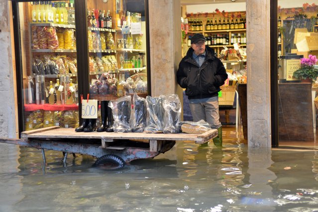 """A shoes seller displays wellies outside his shop in a flooded street during a """"acqua alta"""" on November 11, 2012 in Venice. Rain and wind hit the north of Italy on Sunday and the folooding reached 150 centimetres in Venice. (Photo by Marco Sabadin/AFP Photo)"""