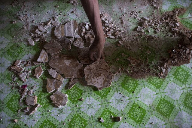 A man collect the pieces of mural painting scattered on the floor at the damaged, ancient Htilominlo Temple on August 25, 2016, after a 6.8 magnitude earthquake hit Bagan. (Photo by Ye Aung Thu/AFP Photo)
